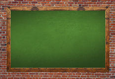 Green blackboard in wooden frame with eraser and chalk on brick Stock Image