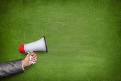 Green blank blackboard with hand holding megaphone Stock Images