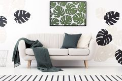 Green blanket and cushion on settee in white living room interior with poster of leaves. Real photo stock images