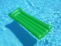 Green on Blue. A green floating lilo on a swimming pool Royalty Free Stock Image