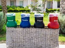 Four recycle bins for waste segregation (glass, paper, metal and plastic). Ecology and recycling concept. Green, blue, black and red trash cans (garbage bins) stock image