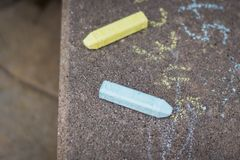 Chalk on sidewalk. Green and blue chalk for children on sidewalk - playful and childlike concepts stock image