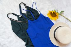 Green and blue dresses, hat and sunflower on white fur. Fashionable concept, top view Royalty Free Stock Images