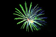 Green and blue fireworks in the sky stock image