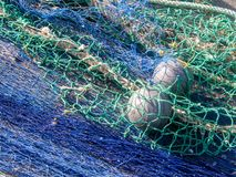 Fishing net with floating buoys. Green blue fishing net with floating buoys and thick white ropes lying at the harbour to dry in the sun royalty free stock photography