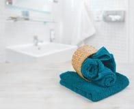 Green-blue folded towels in wicker basket over defocused bathroom stock images