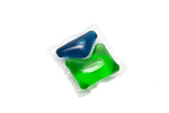 Green and blue gel capsules with laundry detergent Stock Photos