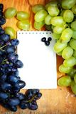 Green and blue grapes. With empty notepad on wooden background Stock Photos