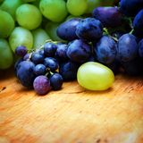 Green and blue grapes. On wooden background Royalty Free Stock Image