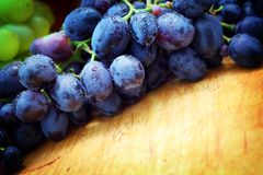 Green and blue grapes. On wooden background Stock Image