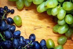 Green and blue grapes. On wooden background Royalty Free Stock Photography