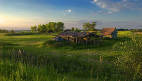 Green and blue landscape at dusk. Beautiful landscape at dusk. You can see small house with red roof, old barn, green meadow and some trees further away royalty free stock photo