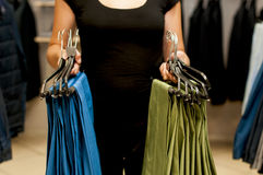 Green and blue men's trousers on hangers in female hands. Royalty Free Stock Image
