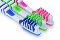 Green, blue and pink toothbrushes are isolated on a white stock photo