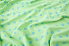Green with blue polka dots wrinkled fabric Stock Photo