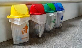 Foue color trash can. Green blue red and yellow Trash can on granite concrete floor Royalty Free Stock Photo