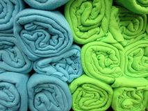 Fleece blankets. Green and blue rolled fleece blankets stock image