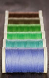 Green and blue spools of thread on dark background Royalty Free Stock Images