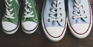 Green and blue textile sneakers on a brown wooden surface royalty free stock images