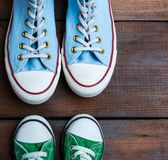 Green and blue textile sneakers on a brown wooden surface stock images
