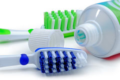 Green, blue toothbrushes and toothpaste isolated on a white back Stock Photos