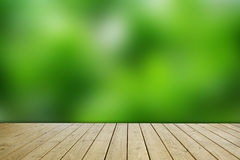 Green blur wall background and brown wooden floor. Stock Photos