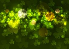 Green blurred bokeh background with clovers Royalty Free Stock Photos