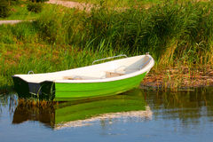 Green boat. On the shore of a lake Royalty Free Stock Image