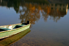 Green boat. Boat and a house reflection Royalty Free Stock Photo