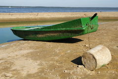 Green boat on the beach. Landscape with old, rusty boat on the beach and lake Royalty Free Stock Image