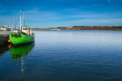 Green boat at dock. Lonely green boat at the dock on a sunny day. Deep blue colored sky and sea Stock Image