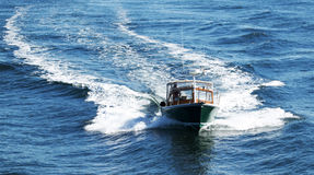 Green boat following in a ferry's wake royalty free stock photography