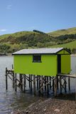 Green boat house on stilts. Green boat house with corrugated roof, window and supported above the sea on stilts Stock Images