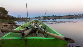 Green boat moored at the shore Stock Photo