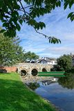 Green Boat on River Christchurch. A green boat floating on the River Avon by a bridge in Christchurch, Dorset, UK Stock Images