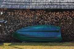 A boat stands at a pile of wood royalty free stock images
