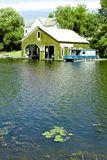 Green Boathouse and Lilly Pads Royalty Free Stock Photography