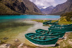 Green boats at glacier lagoon in Peruvian Andes. Huaraz, PERU in November 2015: Six green boats are waiting to be sailed across the blue glacier lagoon in the Royalty Free Stock Images