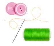 Green bobbin thread with needle and pink buttons Stock Image