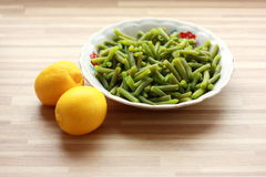 Green boiled bean and yellow lemons. A view of green boiled bean on a traditional plate on the wooden table and two yellow lemons Stock Image