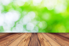 Green bokeh blur background and wood table in garden. With space Royalty Free Stock Image