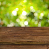 Green bokeh lights background with wooden table Royalty Free Stock Image