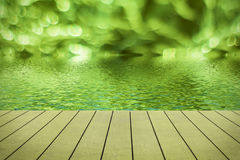 Green bokeh reflected in water. Royalty Free Stock Photography