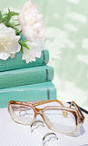 Green books, glass, white flowers on the green flower background. Education card Royalty Free Stock Photo