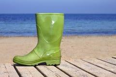 Green boot on beach unlucky fisherman metaphor. Green boot on summer wooden beach soil unlucky fisherman metaphor Stock Photos