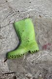 Green boots trash on beach shore pollution Stock Photo