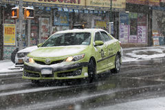 Green Boro Taxi turning during snow storm Stock Photos