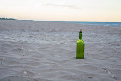 Green Bottle At The Beach On The Sand. Photo of green wine bottle with cork sitting in the sand on the beach. Water and morning sky in the background. Photograph Royalty Free Stock Photography