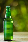 Green bottle of beer with bokeh background Royalty Free Stock Photos