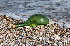 Green bottle with the message. On a shelly beach Stock Photography